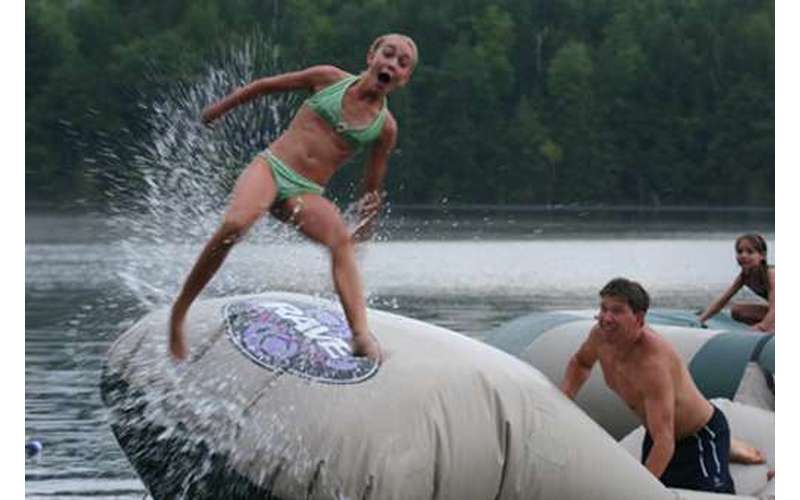 A girl getting bounced off an inflatable raft into the water