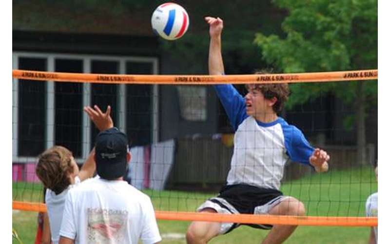 A boy spiking a volleyball over a net to two other boys
