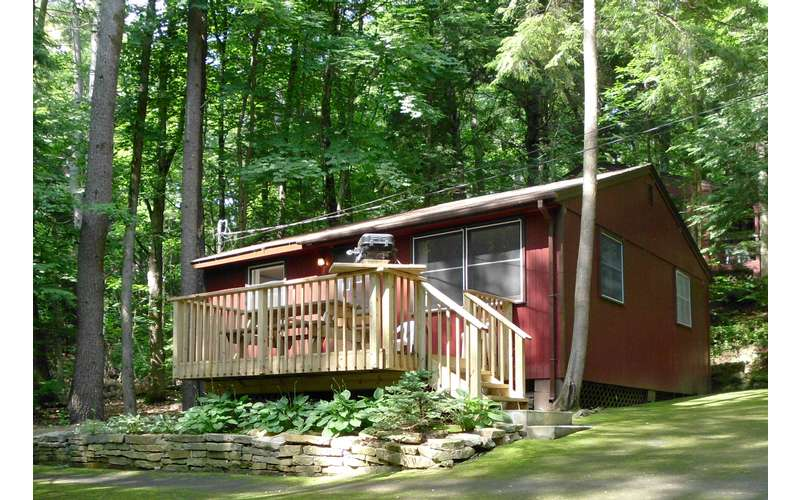 a cabin with a deck with picnic table and grill