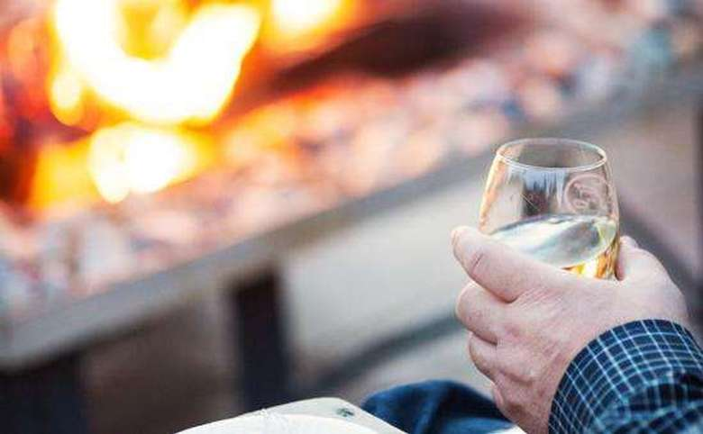 man sitting in front of a fire pit holding a glass of white wine