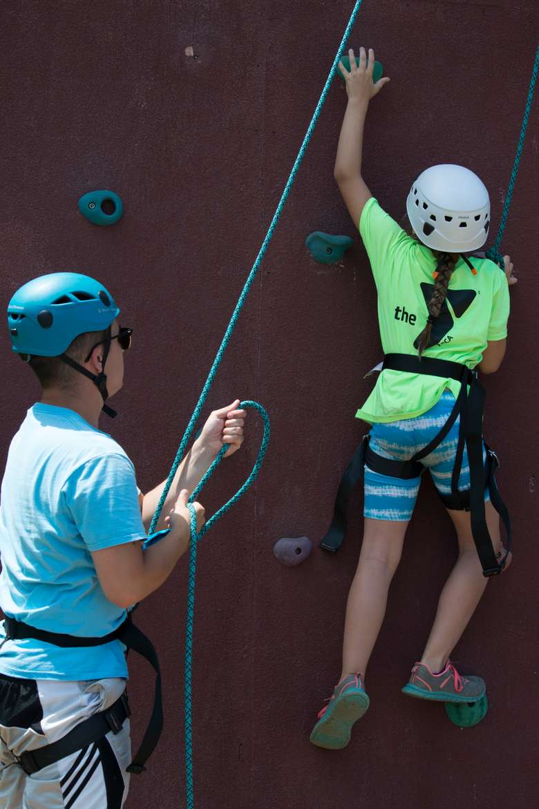 child on a rock climbing wall while a man holds the other end of the support rope