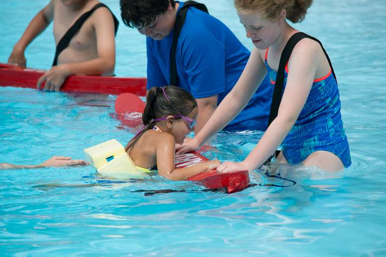 girl in a swim glass with instructors