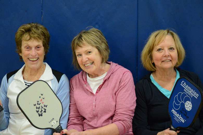 three women smiling and holding pickleball paddles