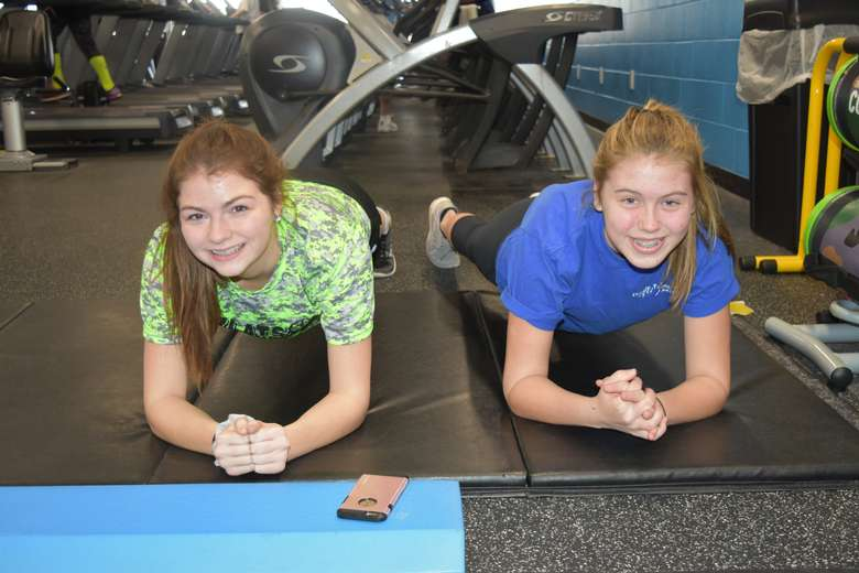 two teenage girls doing planks at the gym