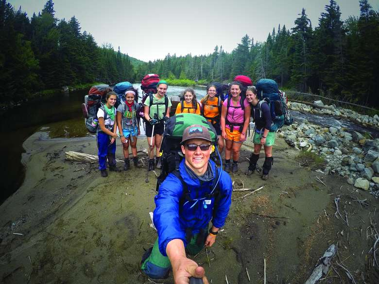 expedition leader using a selfie stick to capture himself and a group of campers with large packs on their backs