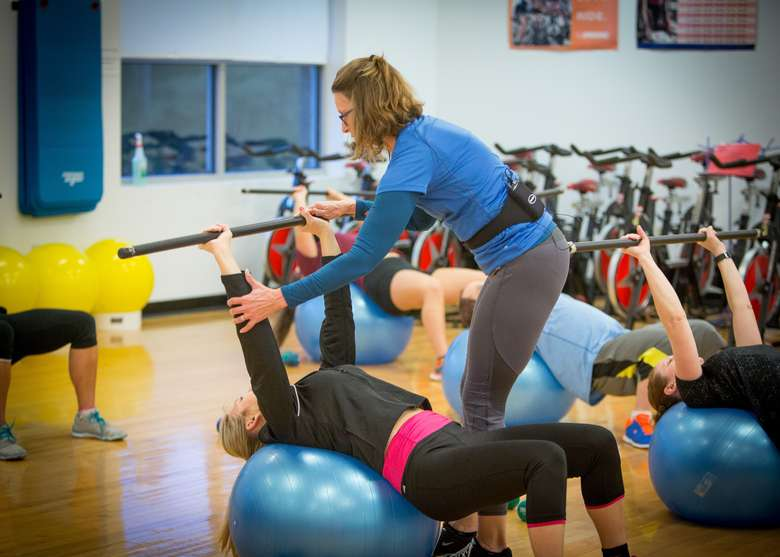 fitness instructor helping a woman laying on a half-ball holding a bar over her head