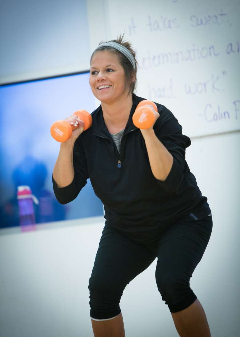 woman holding small weights and doing a squat