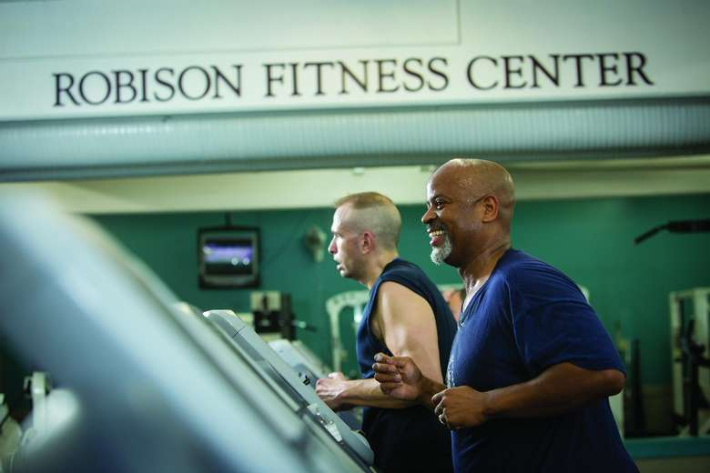 two men running on treadmills with a large sign over their heads that says robison fitness center