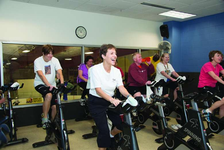 group of happy people in a spin class