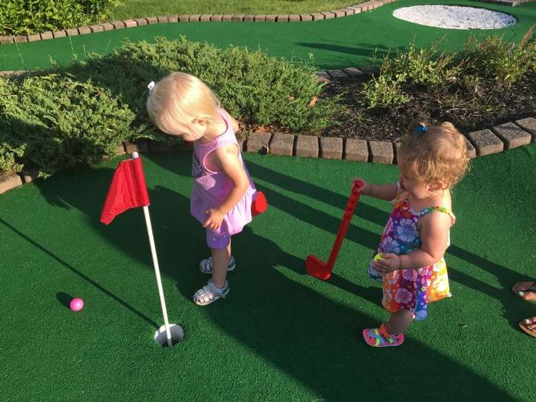 Two young girls playing mini golf