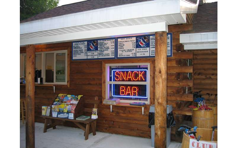 Snack Bar inside a log building with a neon sign