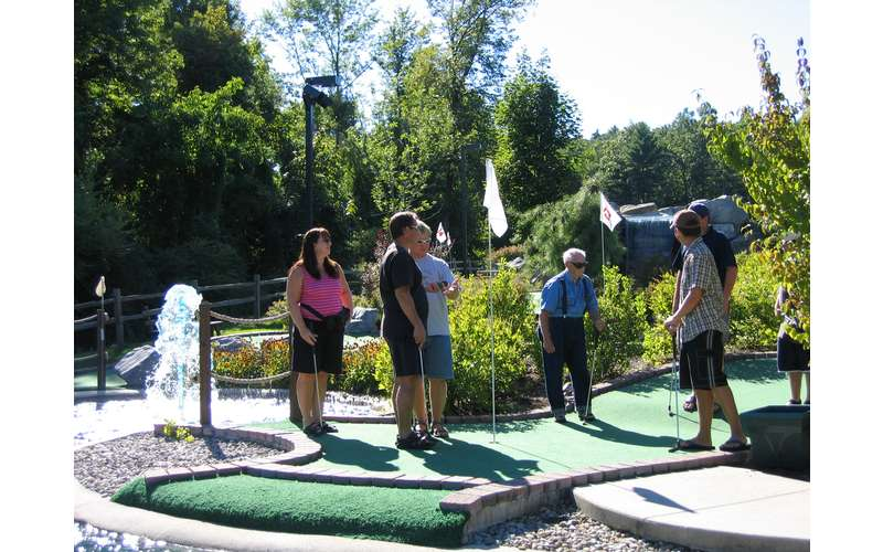 Family playing mini golf next to a water feature