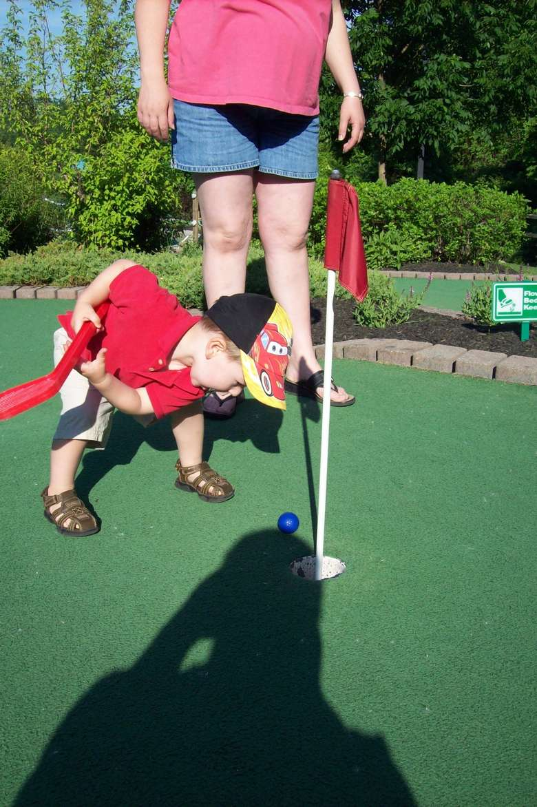 Young boy and his mom playing mini golf