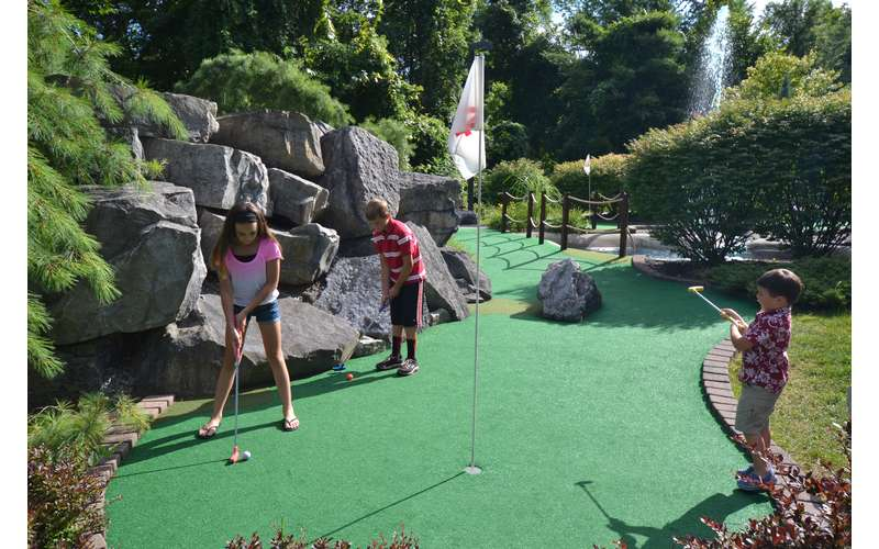 Three kids playing mini golf