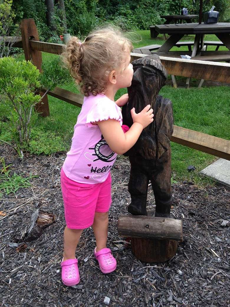 A young girl kissing a statue at Lumberjack Pass