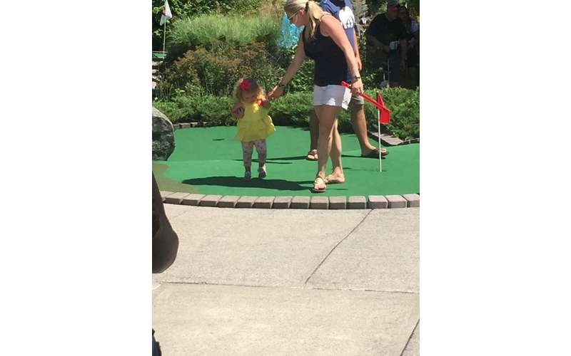 A young girl and her mom walking on a putting green