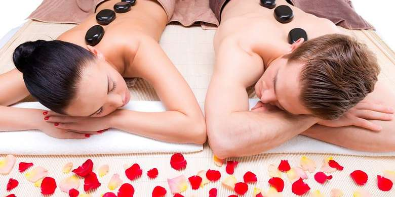 a woman and man getting a stone therapy massage