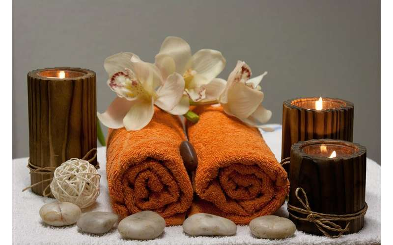 towels, stones, candles, and flowers arranged in a display