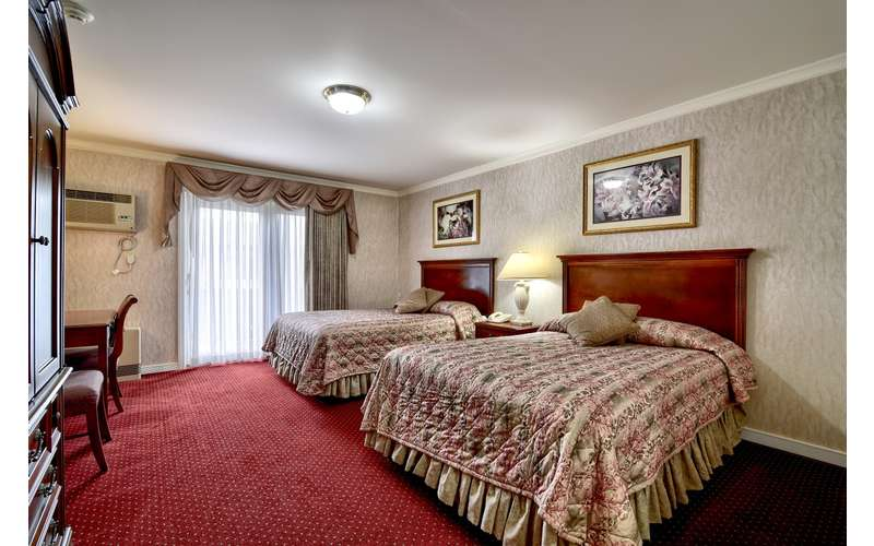 a hotel bedroom with two beds and red carpeting