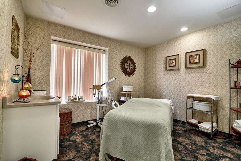a room at a spa with bed, counter, blinds on window