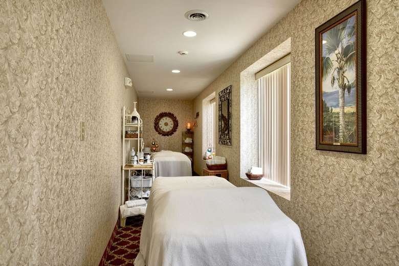 a narrow room at a spa with a bed