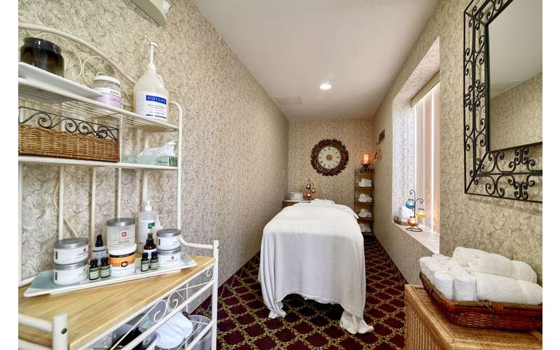 narrow room at a spa with bed, mirror, counter