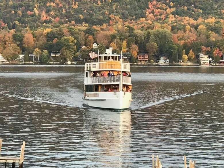 fall colors on trees and cruise ship on water