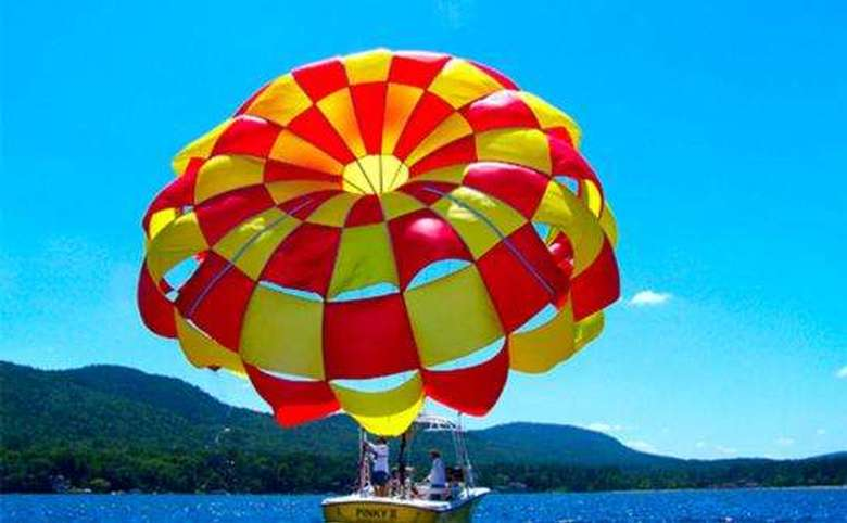red and yellow parasailing parachute ready to launch off the back of a boat