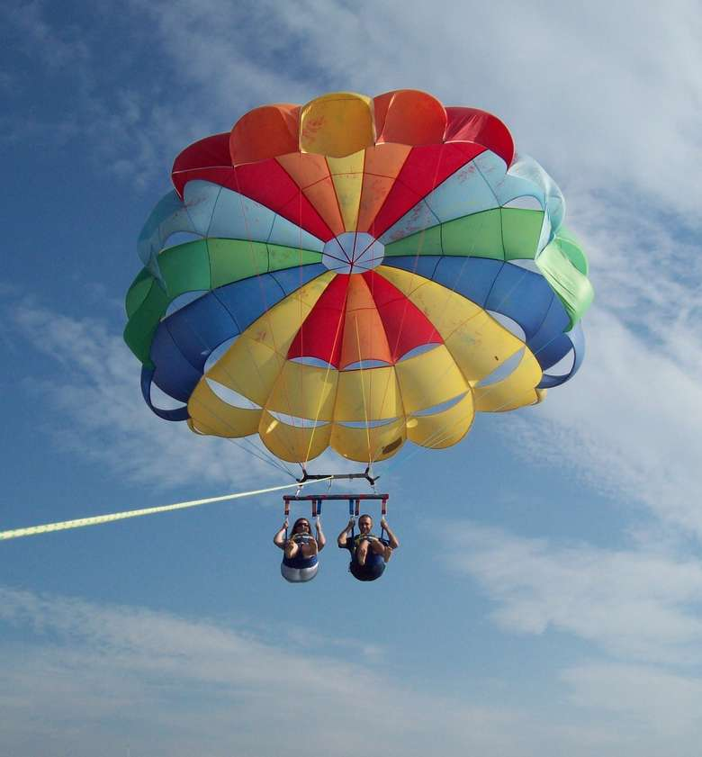rainbow parachute carrying two parasailers behind a boat