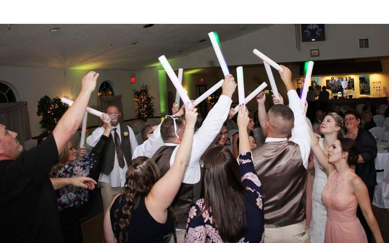 wedding gusts holding up what looks like lasers