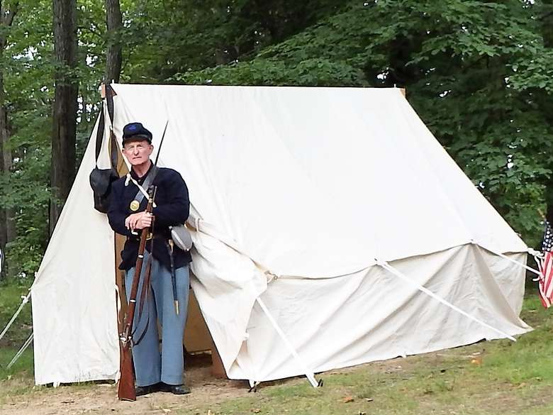 reenactor dressed as a soldier standing outside the entrance of a small white tent
