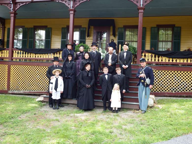 group of reenactors, including both adults and children, dressed up as the grant family posing on the cottage porch