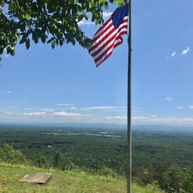 american flag on top of a hill on a sunny day