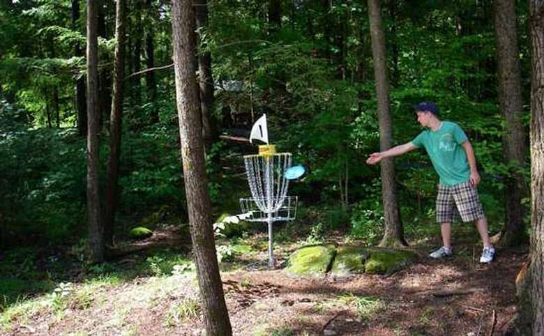 person playing disc golf in the woods