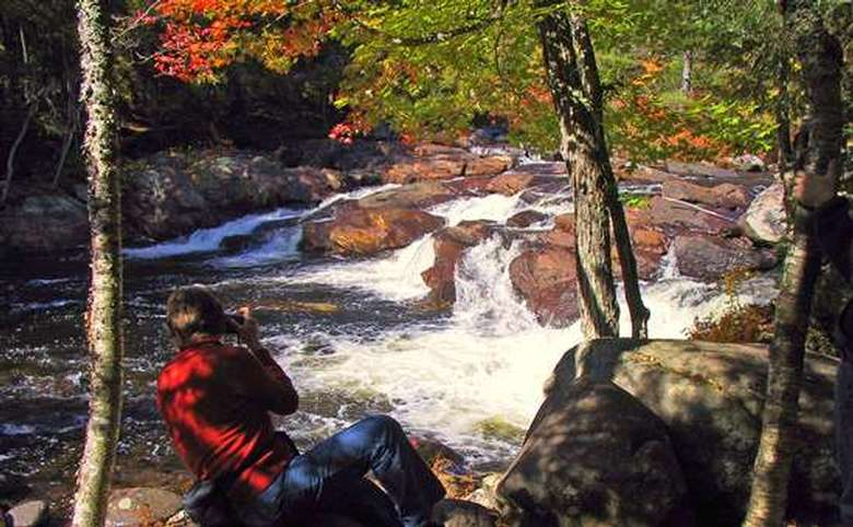person taking a picture of a waterfall in the fall