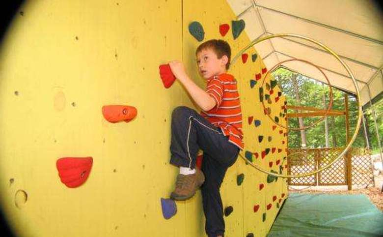 young boy climbing on a rock wall
