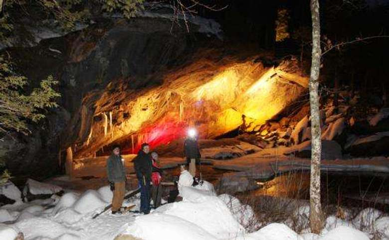 four people snowshoeing in front of a lit cave entrance