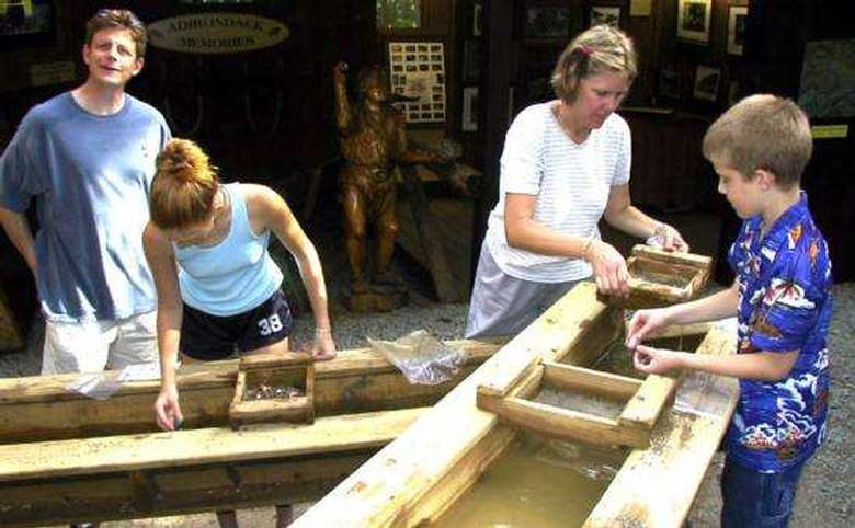 four people mining for gemstones in a trough