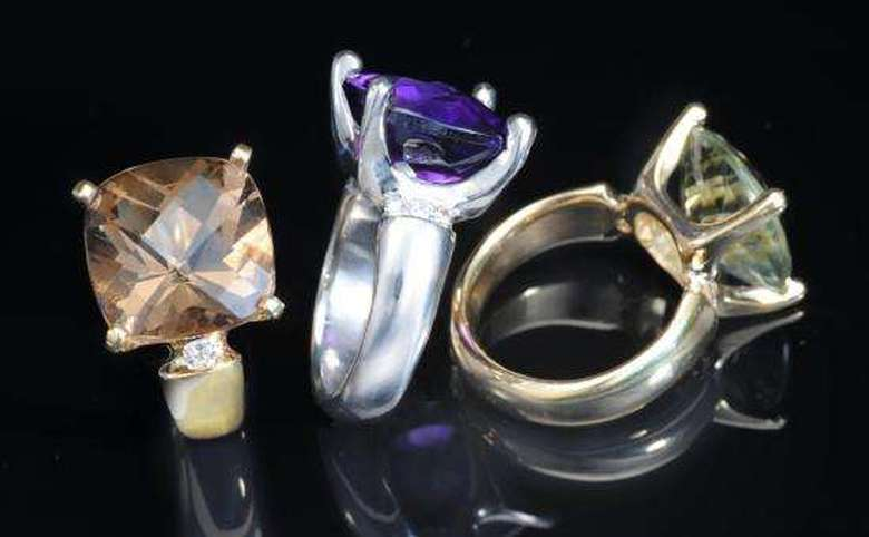 three rings with different stones, topaz, amethyst and peridot