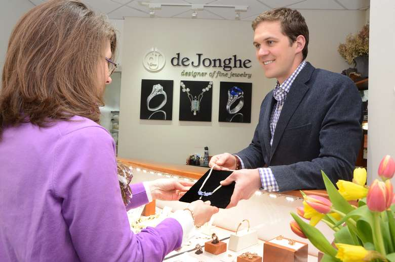 staff member of de Jonghe jewelry store showing a necklace to a customer