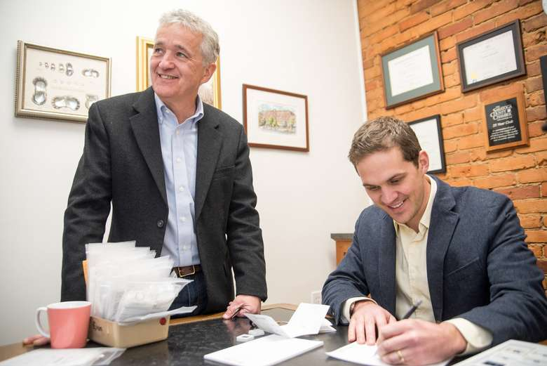 father and son co-owners signing papers in a brick office