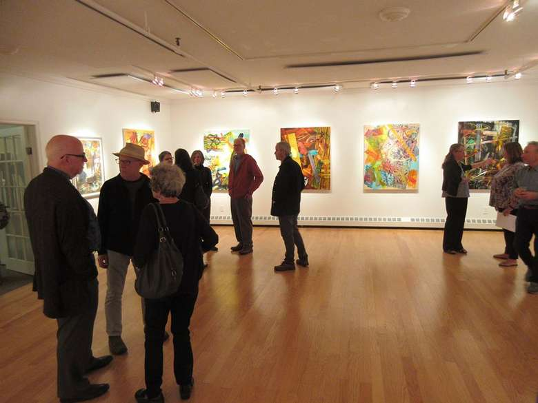 people in a gallery with paintings on the wall