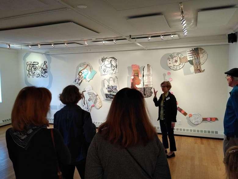 a speaker talking to people in a gallery