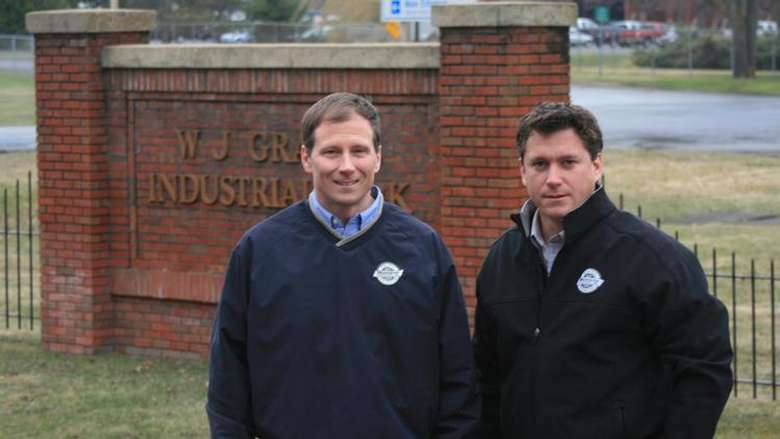 John & Michael Munter in front of industrial park sign
