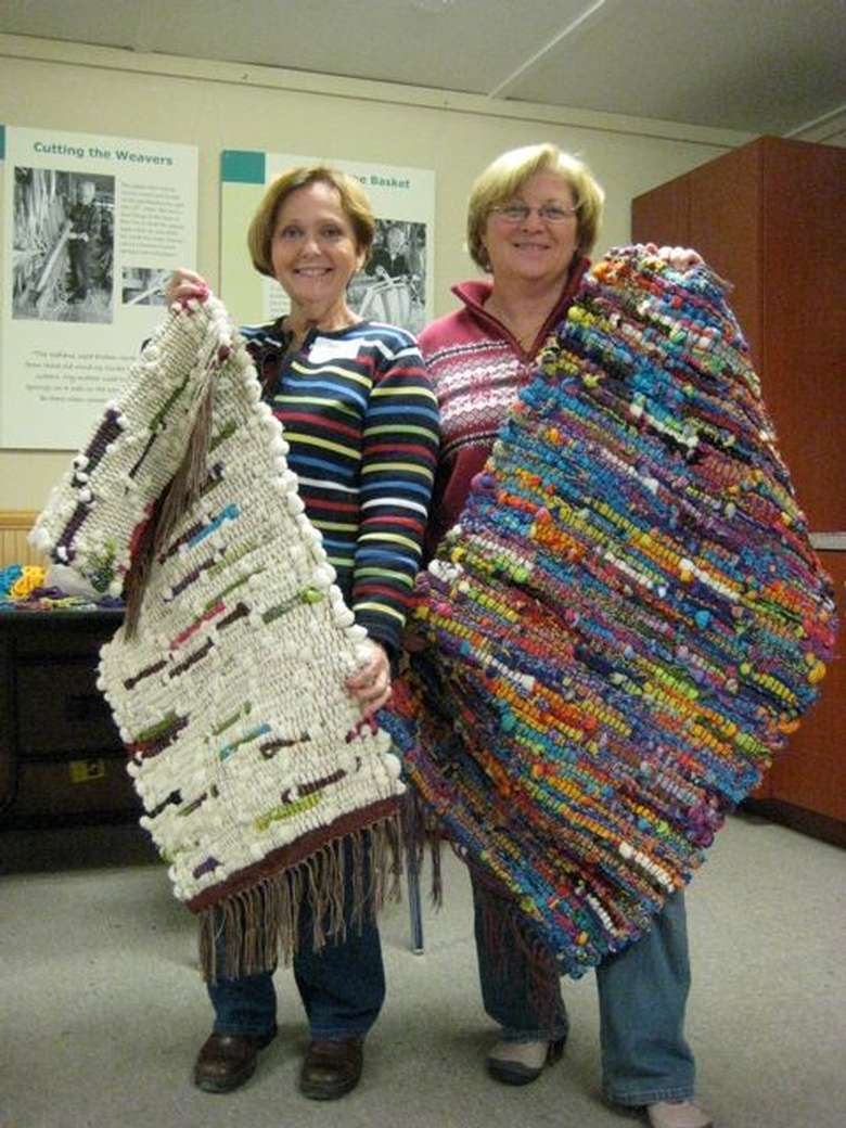 two women holding up colorful rugs