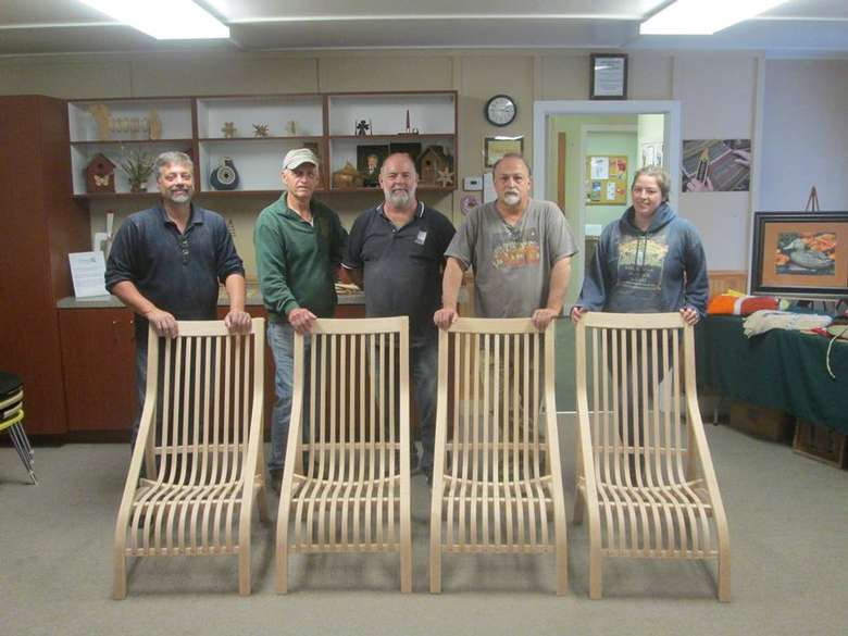 group standing near wooden chairs