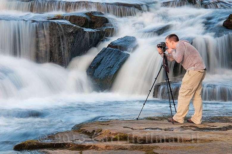 man taking a photo near waterfall