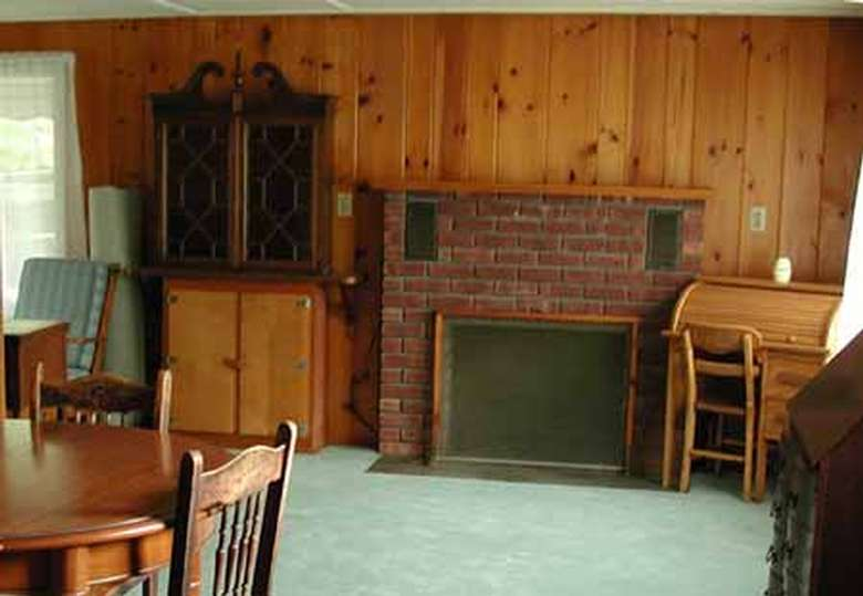 rustic paneled living room with fireplace