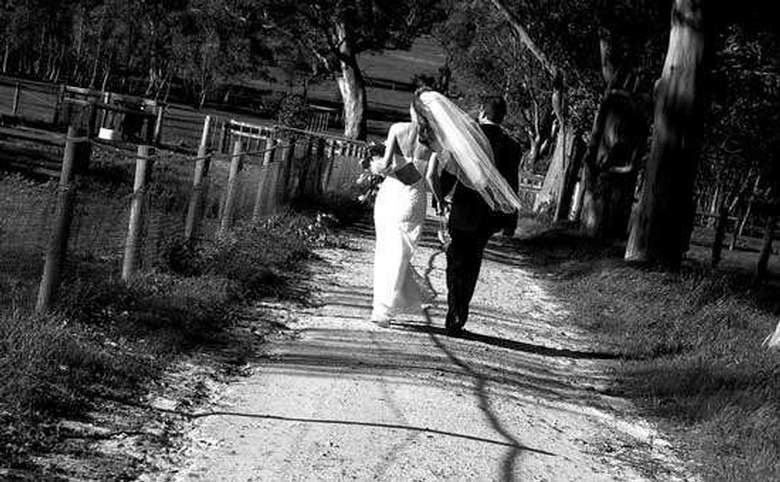 Black and white photo of bride and groom walking away