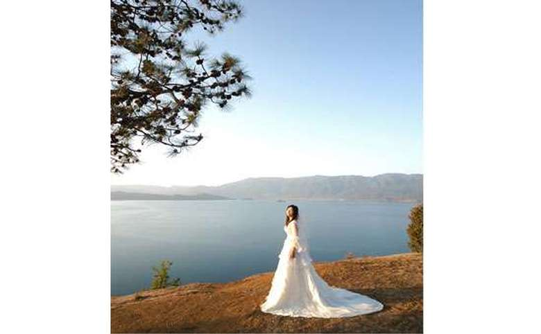 Bride with a long train in front of a lake and surrounding mountains